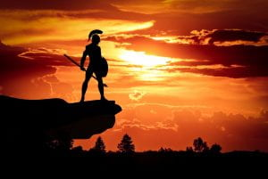 Silhouette of a Spartan warrior overlooking a sunset